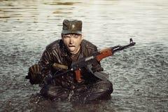 坐在有攻击步枪的湖的制服的疯狂的战士 库存照片