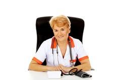 坐在有bloog preasure测量仪的书桌后的微笑年长女性医生或护士 免版税库存照片