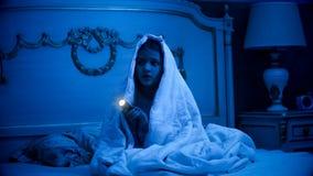 坐在有glashlight的黑暗的卧室的害怕的女孩 库存图片