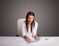 坐在服务台和执行文书工作的女实业家 库存图片