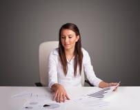 坐在服务台和执行文书工作的女实业家 图库摄影