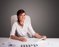 坐在服务台和执行文书工作的女实业家 库存照片