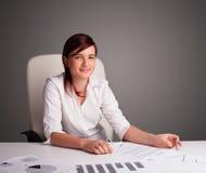 坐在服务台和执行文书工作的女实业家 免版税库存图片
