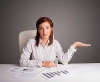 坐在服务台和执行文书工作的女实业家 免版税库存照片