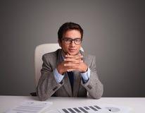 坐在服务台和执行文书工作的生意人 库存图片