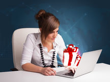 坐在服务台和键入在有当前bo的膝上型计算机的俏丽的夫人 免版税库存照片