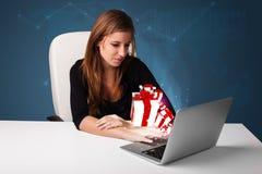 坐在服务台和键入在有当前bo的膝上型计算机的俏丽的夫人 免版税库存图片