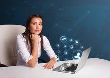 坐在服务台和键入在有社会netw的膝上型计算机的小姐 免版税库存照片