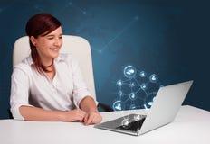 坐在服务台和键入在有社会netw的膝上型计算机的小姐 库存照片