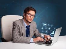 坐在服务台和键入在有社会netwo的膝上型计算机的年轻人 库存图片