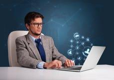 坐在服务台和键入在有社会netwo的膝上型计算机的年轻人 免版税库存照片