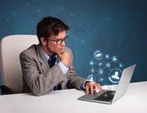 坐在服务台和键入在有社会netwo的膝上型计算机的年轻人 免版税图库摄影