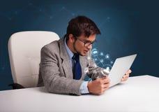 坐在服务台和键入在有社会netwo的膝上型计算机的年轻人 免版税库存图片