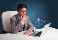 坐在服务台和键入在有社会netwo的膝上型计算机的年轻人 库存照片