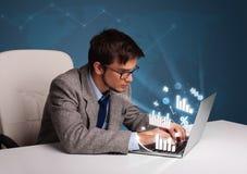 坐在服务台和键入在有绘制的膝上型计算机的年轻人和 免版税库存图片