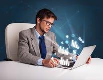 坐在服务台和键入在有绘制的膝上型计算机的年轻人和 库存照片