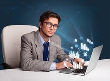 坐在服务台和键入在有绘制的膝上型计算机的年轻人和 免版税图库摄影