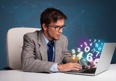 坐在服务台和键入在有3d编号的膝上型计算机的英俊的人 免版税图库摄影