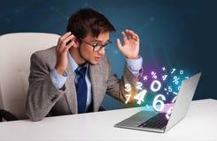 坐在服务台和键入在有3d编号的膝上型计算机的英俊的人 免版税库存照片