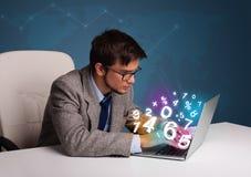 坐在服务台和键入在有3d编号的膝上型计算机的英俊的人 库存图片