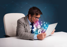 坐在服务台和键入在有3d编号的膝上型计算机的英俊的人 图库摄影