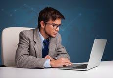 坐在服务台和键入在膝上型计算机的年轻人 库存图片