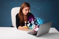 坐在服务台和键入在膝上型计算机的美丽的少妇与 库存图片