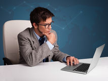 坐在服务台和键入在膝上型计算机的年轻人 免版税图库摄影