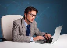 坐在服务台和键入在膝上型计算机的年轻人 图库摄影