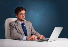 坐在服务台和键入在膝上型计算机的年轻人 免版税库存图片