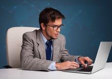 坐在服务台和键入在膝上型计算机的年轻人 免版税库存照片
