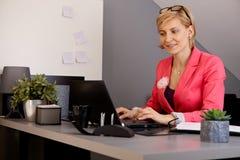 坐在服务台的女实业家 免版税库存照片