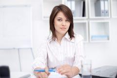 坐在服务台的新女商人在办公室 库存图片
