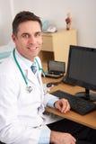 坐在服务台的美国医生 免版税库存照片