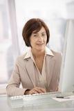 坐在服务台的高级职业妇女 库存照片