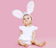 坐在服装复活节兔子的甜桃红色逗人喜爱的婴孩 库存图片