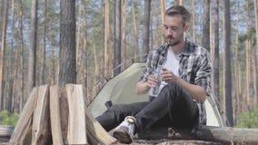 坐在木头的年轻帅哥火的前面,从塑料瓶的饮用水 帐篷 股票录像