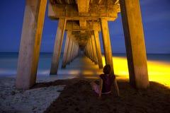 坐在木板走道下的妇女在晚上 免版税图库摄影