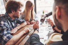 坐在木桌上的小组创造性的multietnic朋友 获得的人们乐趣,当打棋时 图库摄影