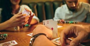 坐在木桌上的朋友侧视图照片  获得的朋友乐趣,当打棋时 免版税库存照片
