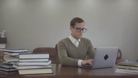 坐在木桌上的玻璃的画象可爱的人在办公室,许多书是在桌上 逗人喜爱的书呆子 影视素材