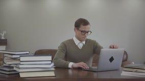 坐在木桌上的玻璃的画象逗人喜爱的书呆子在办公室,许多书是在桌上 可爱的人 股票视频