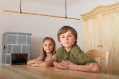 坐在木桌后的孩子 免版税库存照片