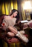 坐在木椅子和读在葡萄酒场面的性感的妇女 免版税库存照片