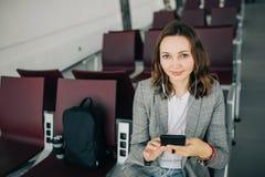 坐在机场的女孩,拿着智能手机 免版税库存照片
