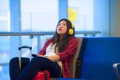 坐在机场离开登机门等待的飞行的年轻愉快和相当亚裔中国旅游妇女使用耳机 免版税库存图片