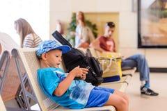 坐在机场离开大厅里的小男孩 免版税库存照片
