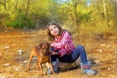 坐在杉木森林里的女孩拿着小犬座 免版税库存图片