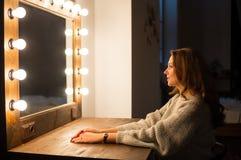 坐在构成镜子前面的妇女 免版税库存图片