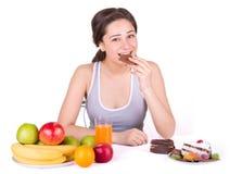 坐在果子和甜点和叮咬巧克力附近的女孩 免版税库存图片